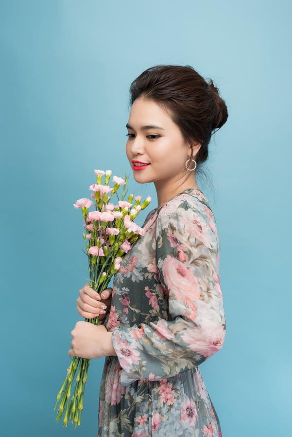 De aantrekkelijke vrouw van Azië in het romantische boeket van de kledingsholding van bloemen over blauwe achtergrond stock fotografie