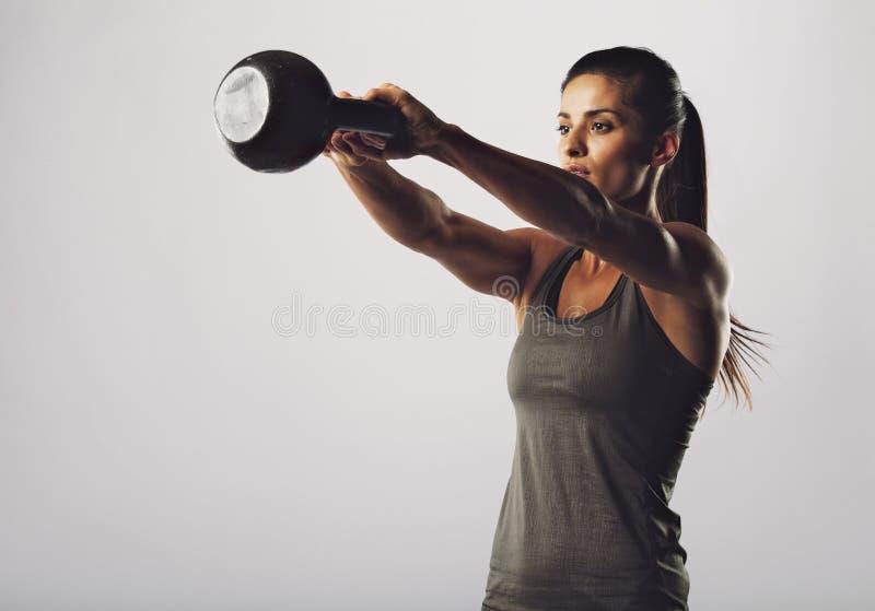 De aantrekkelijke vrouwelijke het doen oefening van de ketelklok stock foto