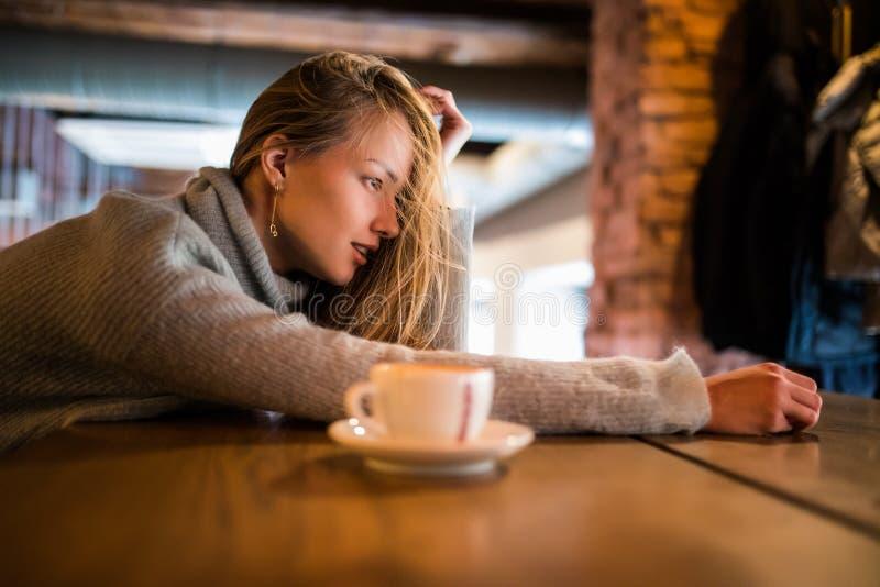De aantrekkelijke vrouwelijke student zit bij koffie met kop van koffie, wil en uitgeputte rust hebben die, worden vermoeid Dream royalty-vrije stock afbeeldingen