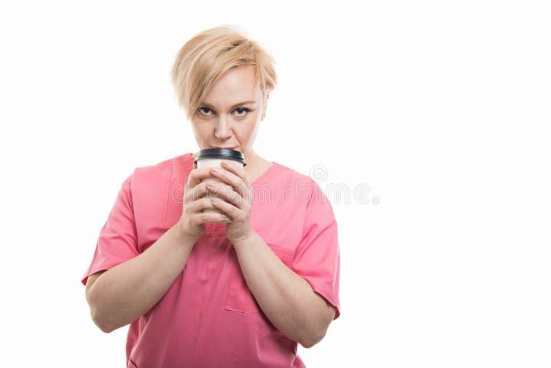 De aantrekkelijke vrouwelijke verpleegster die roze dragen schrobt holdings meeneemcof stock foto