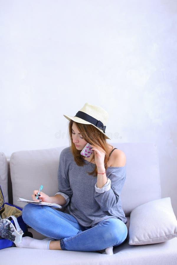 De aantrekkelijke vrouwenbesprekingen op cel telefoneren met vriend en schrijft aan n stock foto's
