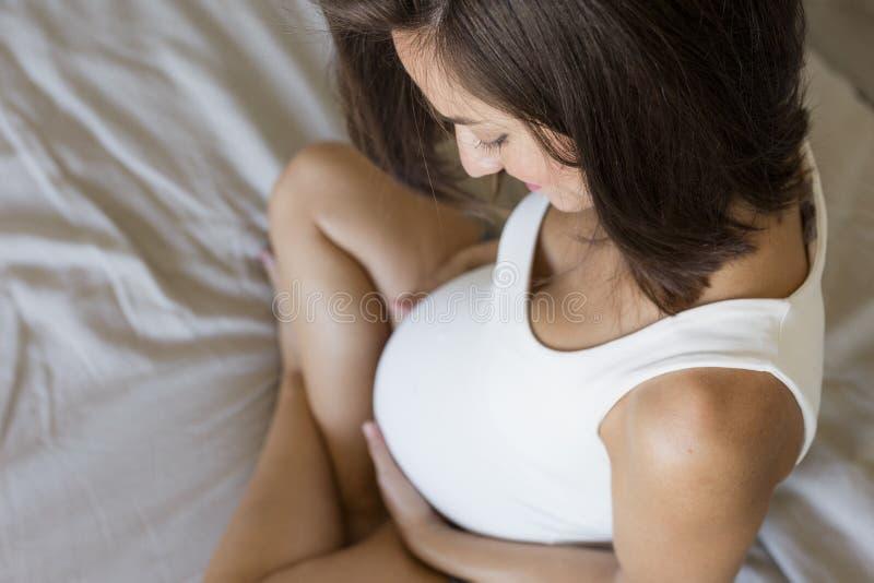 De aantrekkelijke zwangere vrouw zit in bed, het houden van haar buik en het glimlachen Vorige maanden van zwangerschap Levenssti stock foto