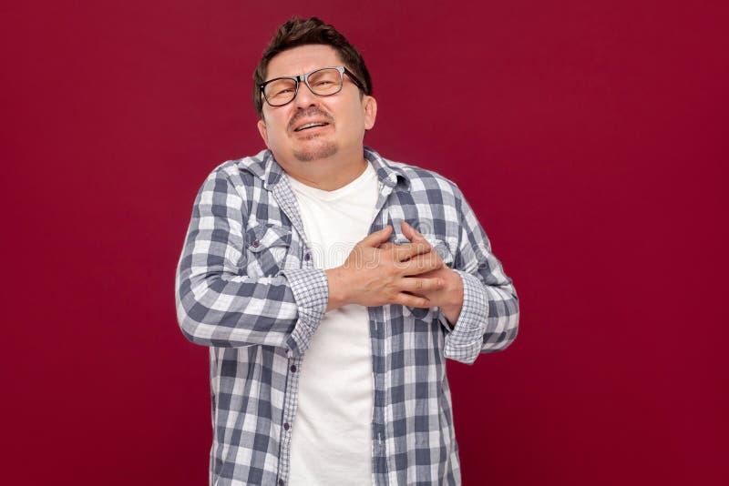 De aanval of het infarct van de hartpijn Portret van de midden oude mens in toevallig geruit overhemd en oogglazen die en van hem stock afbeelding