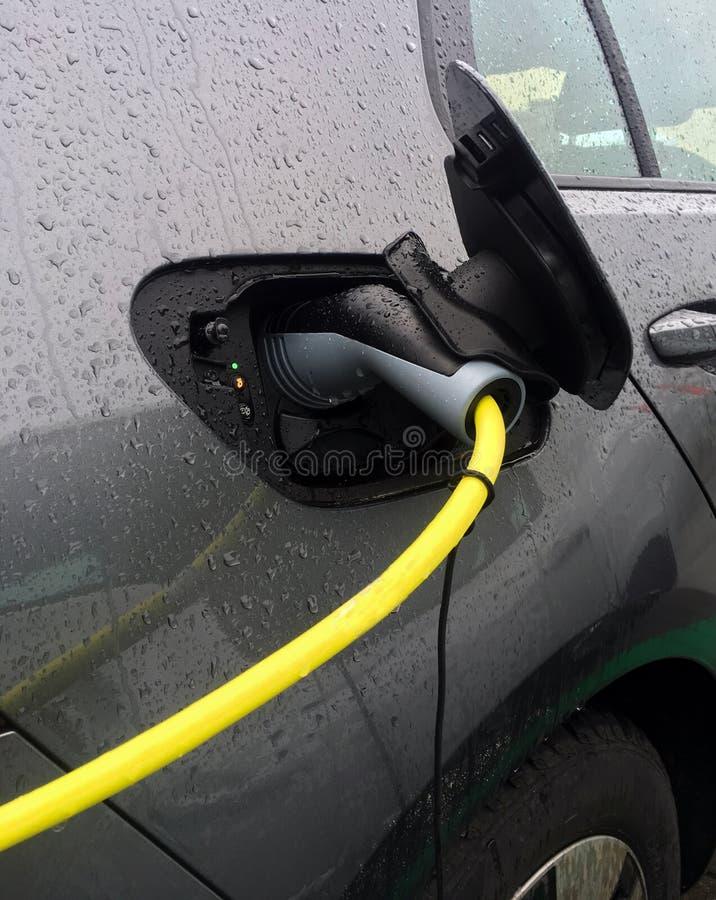 De aanvulling van een elektrische auto stock afbeeldingen