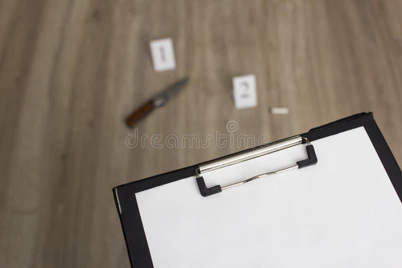 De aanwijzingen een vouwend mes en een sigaret steken op een houten achtergrond, een onderzoek, een leeg blad op een plaque uit stock fotografie