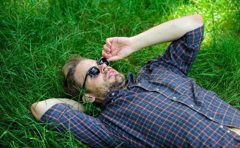 De aard vult hem met versheid en inspiratie Legt de mensen ongeschoren kerel op groene grasweide Natuurlijke versheid Mens stock afbeelding
