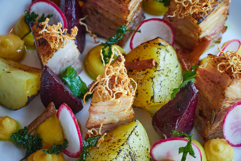 De aardappel in de schilplakken en de bieten met groenten en het bacon van het braadstukvarkensvlees sluiten omhoog stock afbeelding