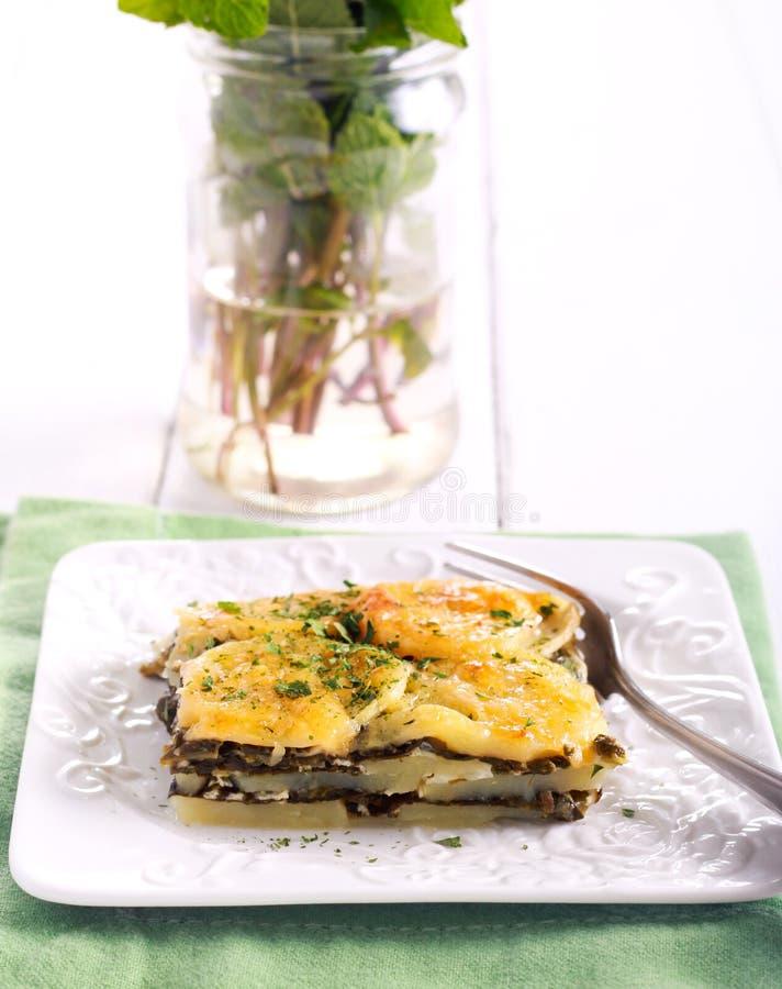 De aardappel en de spinazie bakken stock afbeeldingen
