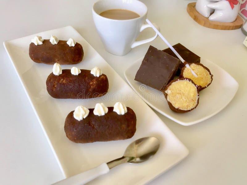De aardappelcake, besnoeiing in cake twee knalt en chocoladestukken Lig op de platen Dichtbij is een kop van koffie met melk stock fotografie
