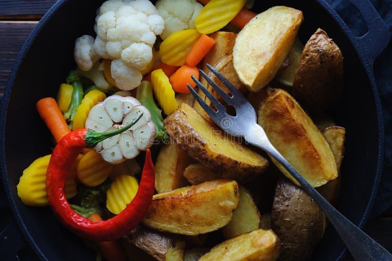 De aardappelen in de schil van het land met groenten in een braadpan stock afbeelding