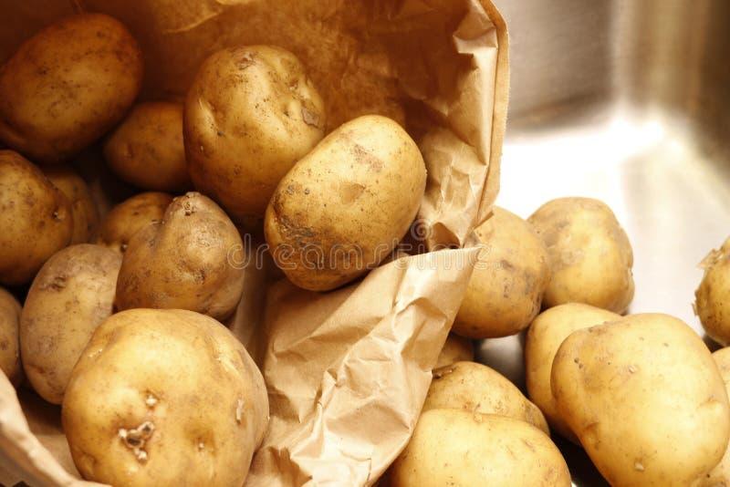 De aardappels in een keukengootsteen goten van een document zak uit royalty-vrije stock fotografie