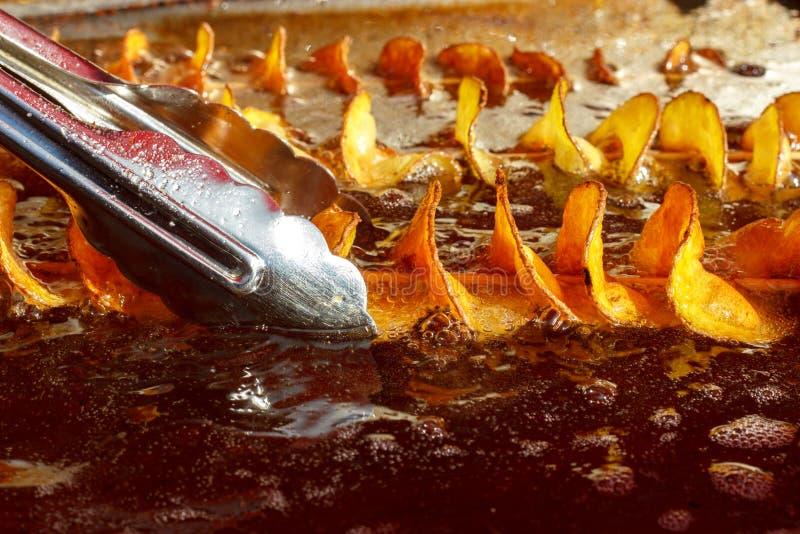 De aardappels zijn gebraden in kokende olie stock fotografie