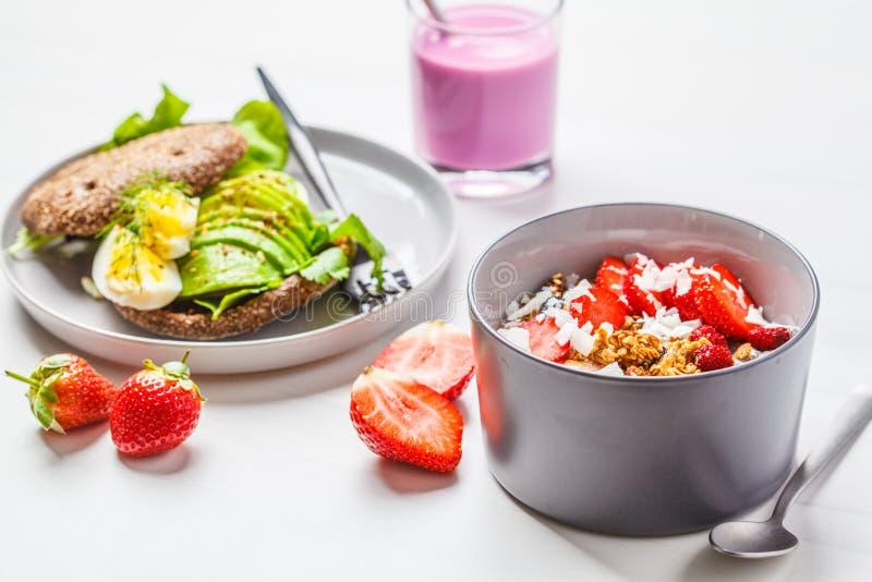 De aardbei smoothie kom met granola, de kokosnoot, de bessen en de avocado roosteren op een witte achtergrond veganistontbijt royalty-vrije stock foto