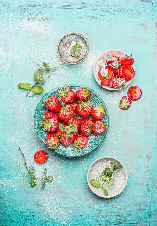 De aardbeien dienden in blauwe kom met muntbladeren en poederden suiker op sjofele elegante houten achtergrond stock afbeeldingen