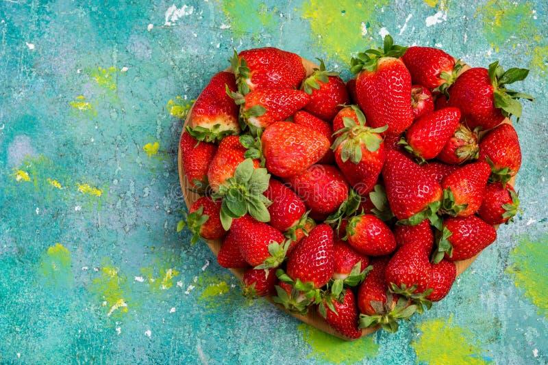 De aardbeien van de hartvorm op houten kleurrijke lijst, liefde voor verse vruchten stock foto