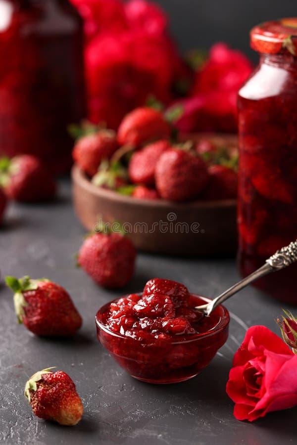 De aardbeijam in a kan en verse aardbeien op een donkere achtergrond, de zomeroogst stock afbeelding