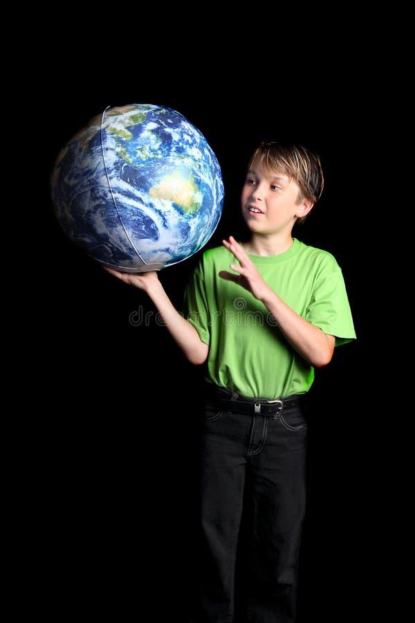 De Aarde van de jongen in zijn hand kijkt met wonder fascinatio royalty-vrije stock foto's