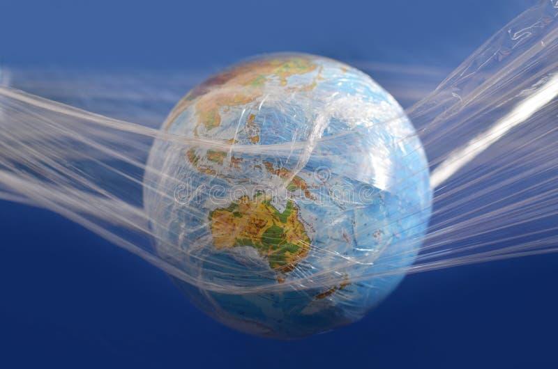 De aarde wordt opgeschort in een plastic plastic beschikbare verpakking, op een blauwe achtergrond Het concept milieuvervuiling d royalty-vrije stock afbeelding
