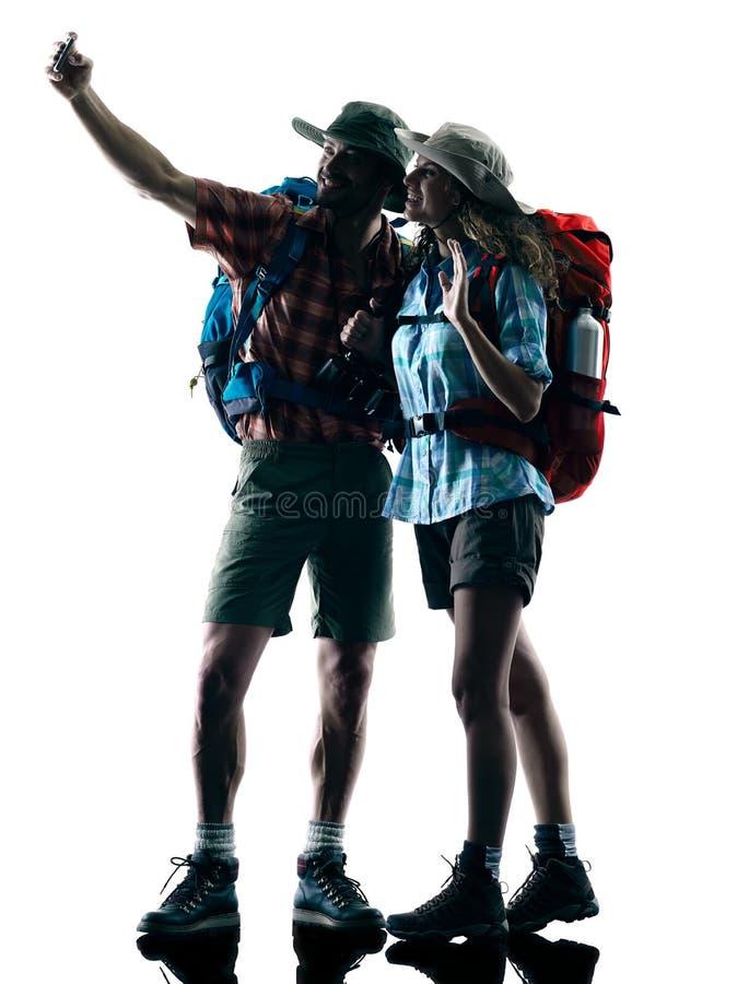 De aardsilhouet van de paar trekker trekking selfie royalty-vrije stock foto's