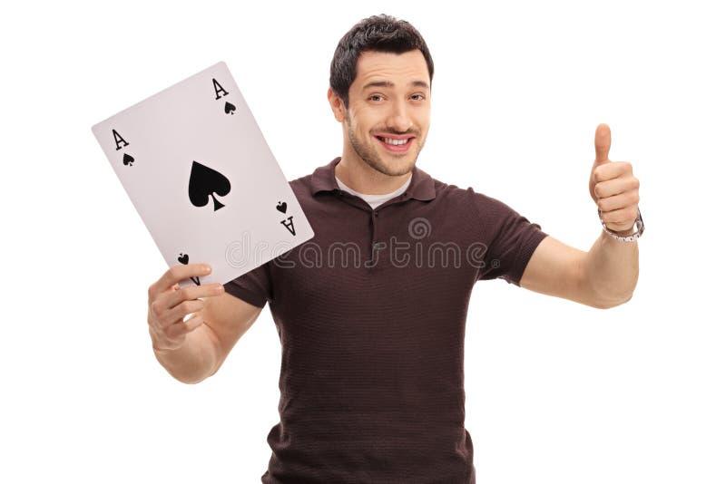 De aas van de kerelholding van spades kaart en het opgeven van duim stock foto
