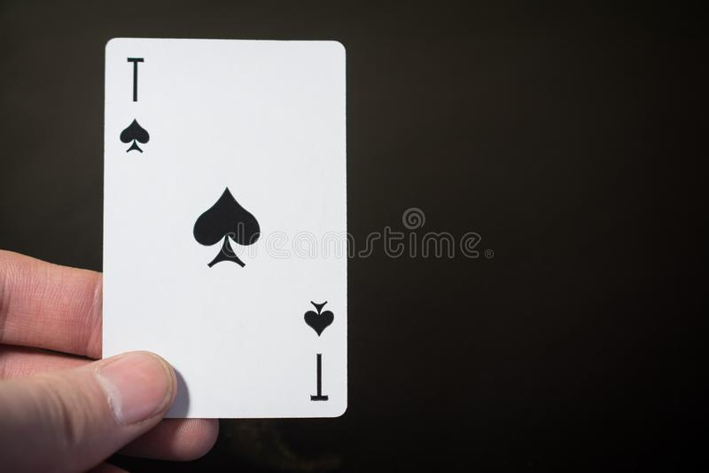 De aas van de de holdingsspeelkaart van de mensenhand van spades op zwarte achtergrond met copyspacesamenvatting die worden geïso stock fotografie