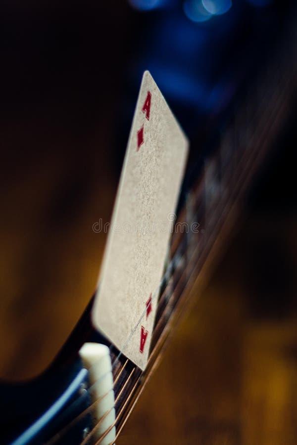 De aas van spades wordt vastgeklemd tussen de koorden van een gitaar royalty-vrije stock fotografie