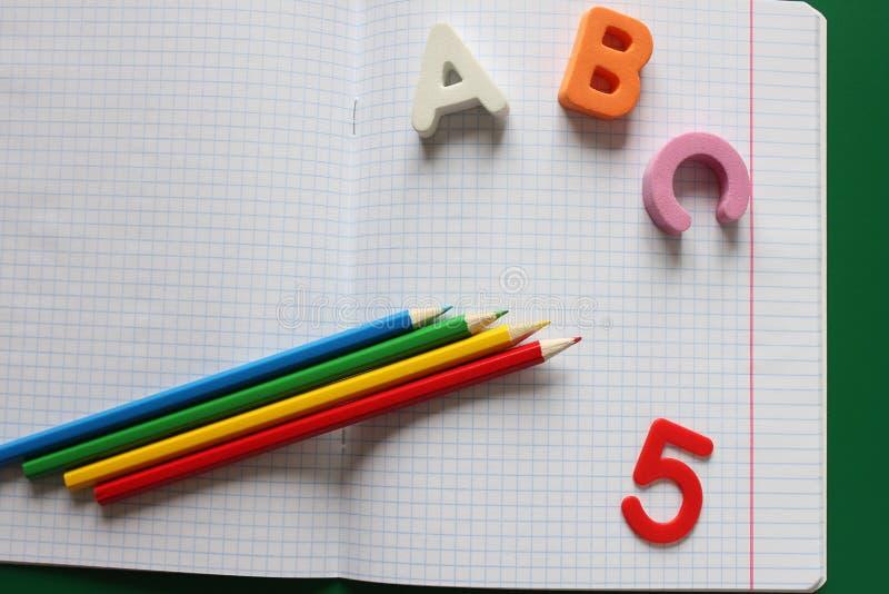 De abc-eerste brieven van het Engelse alfabet en de kleurpotloden op het schoolnotitieboekje, score vijf stock fotografie