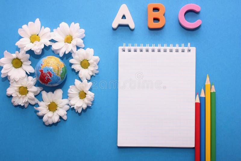 De abc-eerste brieven van het Engelse alfabet op een blauwe achtergrond naast de kleine bol en de witte chrysanten Notitieboekje  royalty-vrije stock foto's