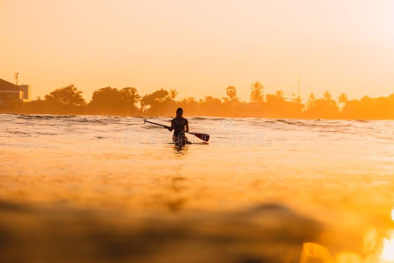 12 de abril de 2019 Bali, Indonesia Lev?ntese a la persona que practica surf de la paleta en tablero del SORBO en el oc?ano Lev?n imagenes de archivo