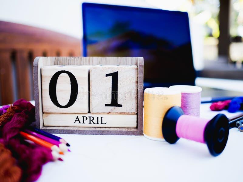 01 de abril Día tonto calendario de madera nuevo año con equipo de coser y smartphone sobre fondo blanco con espacio en blanco imagenes de archivo