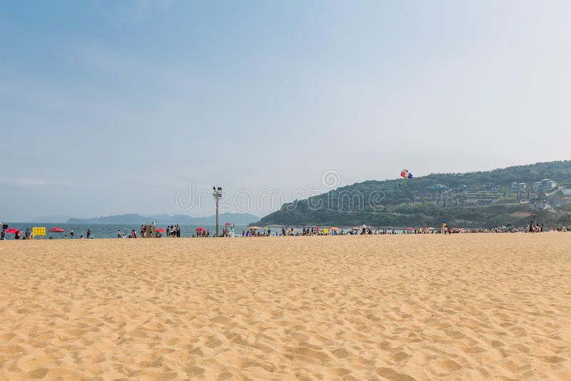 15 de abril de 2014: no meio-dia na praia em Dameisha, um grupo de povos não identificados que jogam, não está absolutamente cert imagens de stock