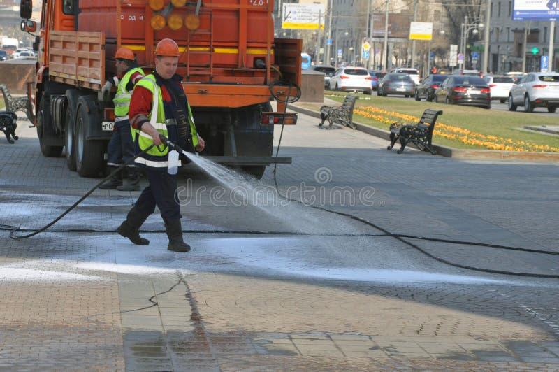 20 de abril de 2019: Moscou, Rússia - os trabalhadores lavam a área pedestre com detergentes fotografia de stock royalty free