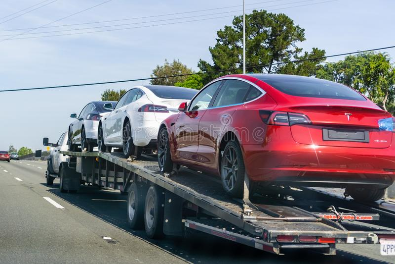 26 de abril de 2019 Redwood City/CA/los E.E.U.U. - el transportador del coche lleva Tesla Model 3 nuevos veh?culos a lo largo de  fotos de archivo libres de regalías
