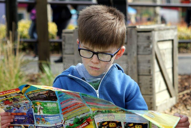 4 de abril de 2016 - Windsor, Reino Unido: Um menino novo estuda o mapa do parque temático de Legoland imagens de stock royalty free