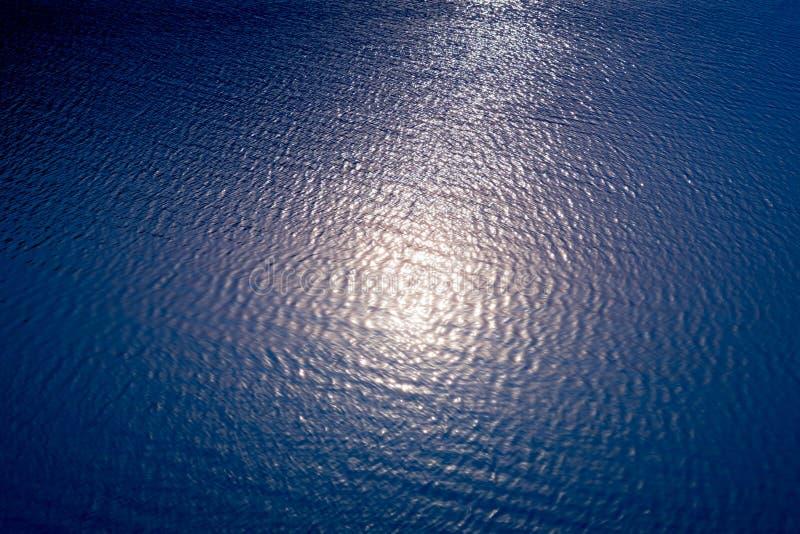 De abstracte bezinning van de onduidelijk beeldzon over het water in het meer stock foto's