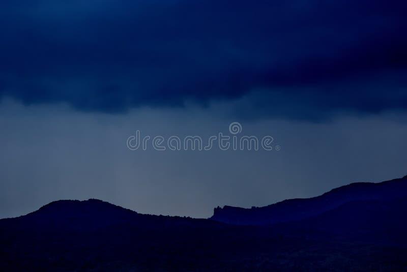De abstracte donkerblauwe aard als achtergrond met een silhouet van de bergen en de regen betrekt stock afbeelding