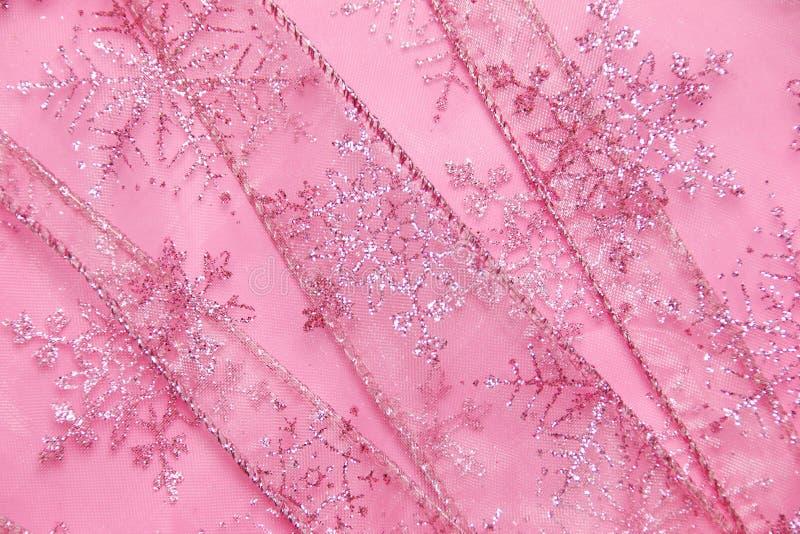 De abstracte geweven achtergrond van roze netto lint met schittert sneeuwvlokken stock foto's
