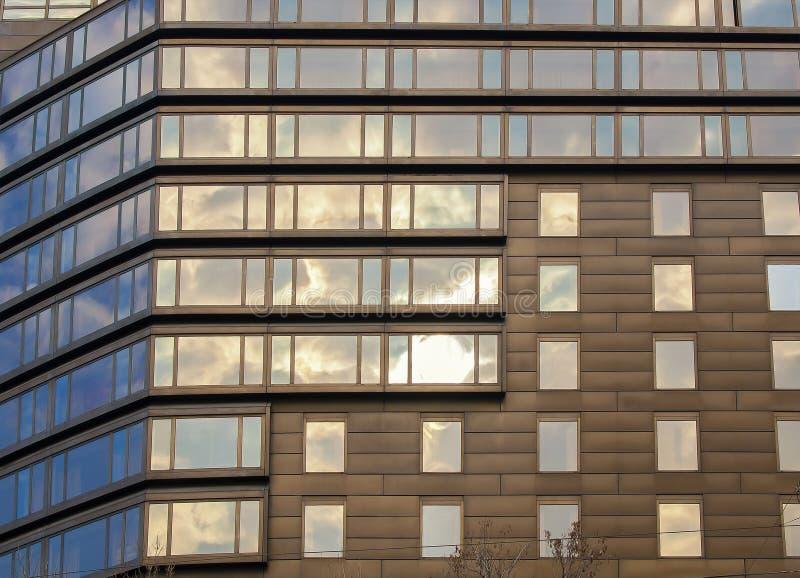 De abstracte moderne voorgevel van het bureauhuis met vensters bij de hemelbezinning royalty-vrije stock fotografie
