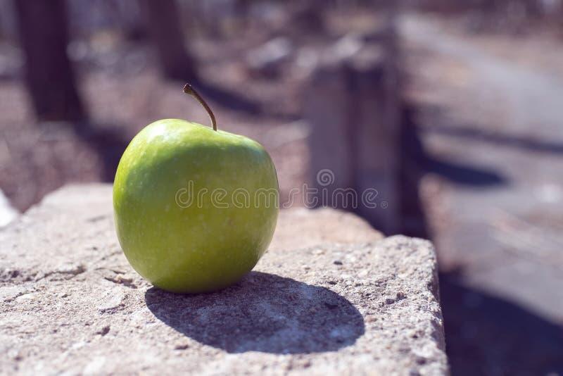 De abstractie op een concrete richel is een groene appel op de eigenlijke rand stock fotografie