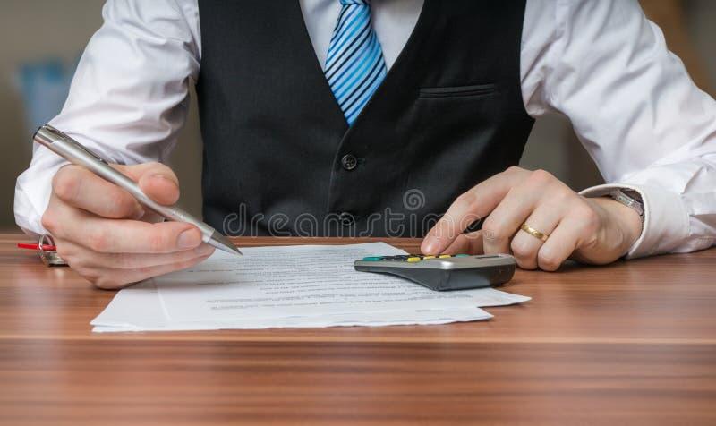 De accountant of de bedrijfsmens berekenen belastingen met calculator stock foto