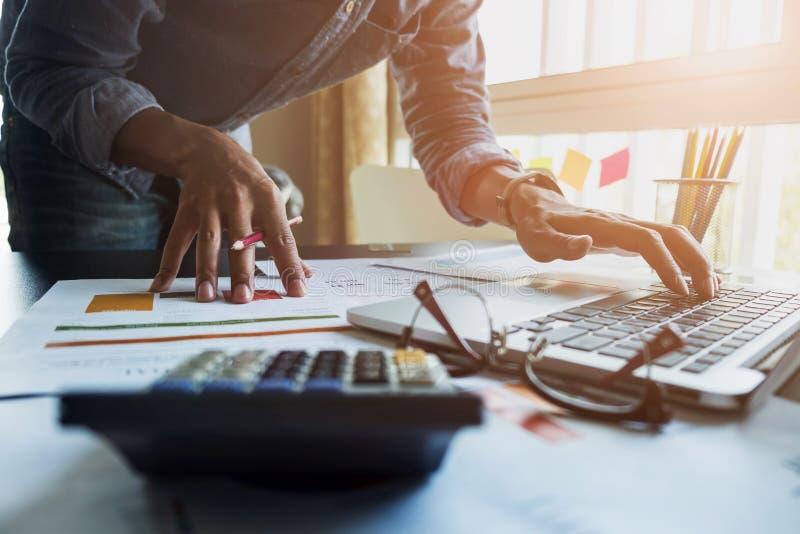 De accountants werken het analyseren van financiële verslagen op laptop bij van hem royalty-vrije stock afbeelding