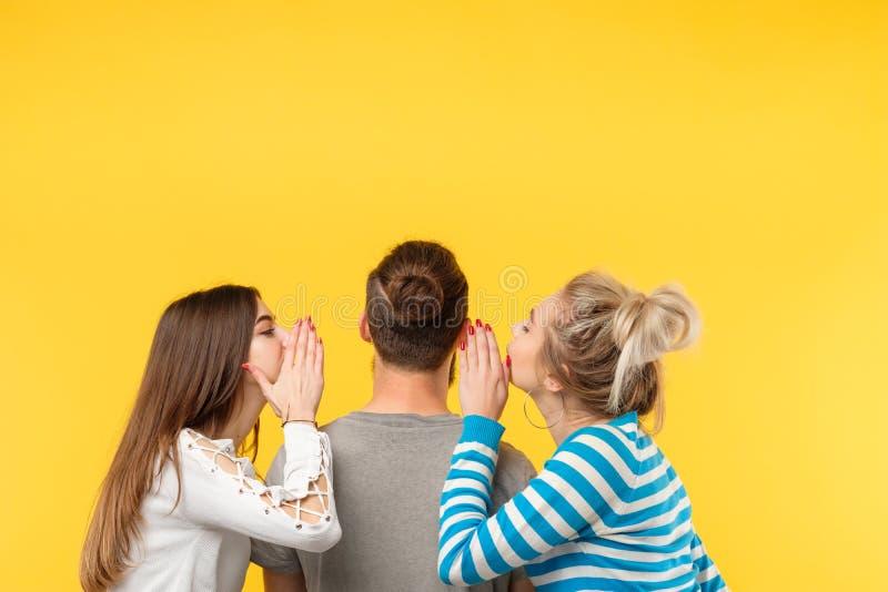 De achter gele man van het gefluistergeheimen van menings tienervrouwen stock foto's