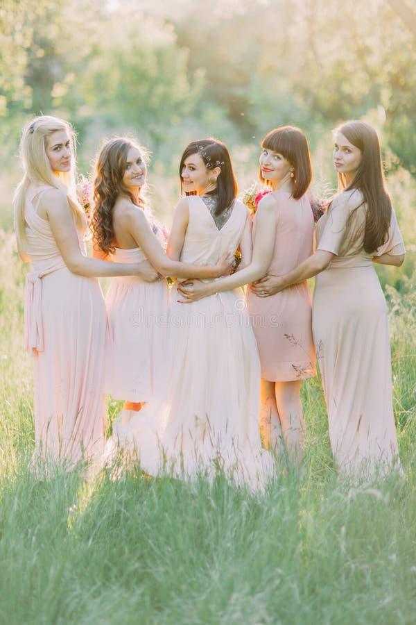De achterfoto van de bruid en haar bruidsmeisjes die erachter in het zonnige bos kijken de zwarte tatoegering op de bruiden stock foto