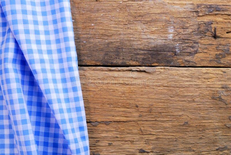 De achtergrond maakte van geruit servet op oude houten lijst royalty-vrije stock afbeelding