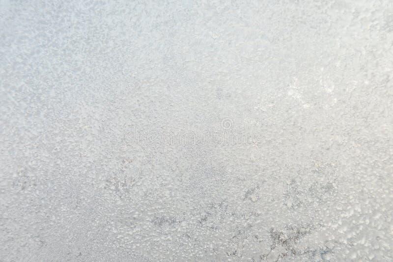 De achtergrond of de textuur van hoar of de rijp op het glazen venster stock afbeeldingen