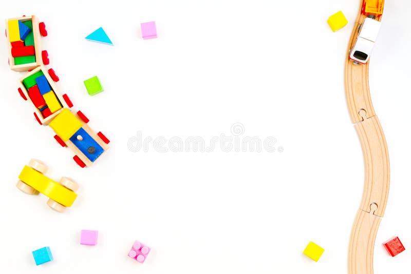 De achtergrond van babyjonge geitjes toyd Houten trein en sporen, stuk speelgoed auto, kleurrijke blokken op witte achtergrond royalty-vrije stock afbeeldingen