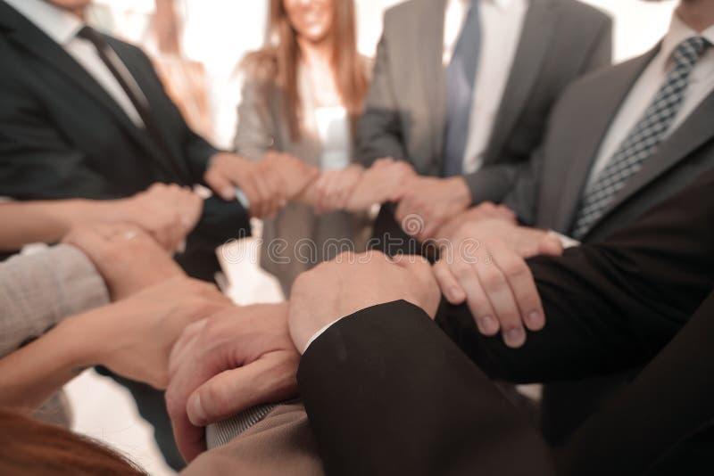 De achtergrond van commercieel team vouwde hun handen vormt een cirkel stock fotografie