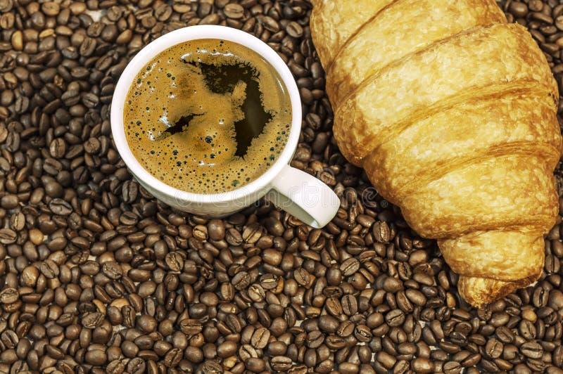De achtergrond van de koffieboon met kop van vers heet koffie en croissant stock afbeelding