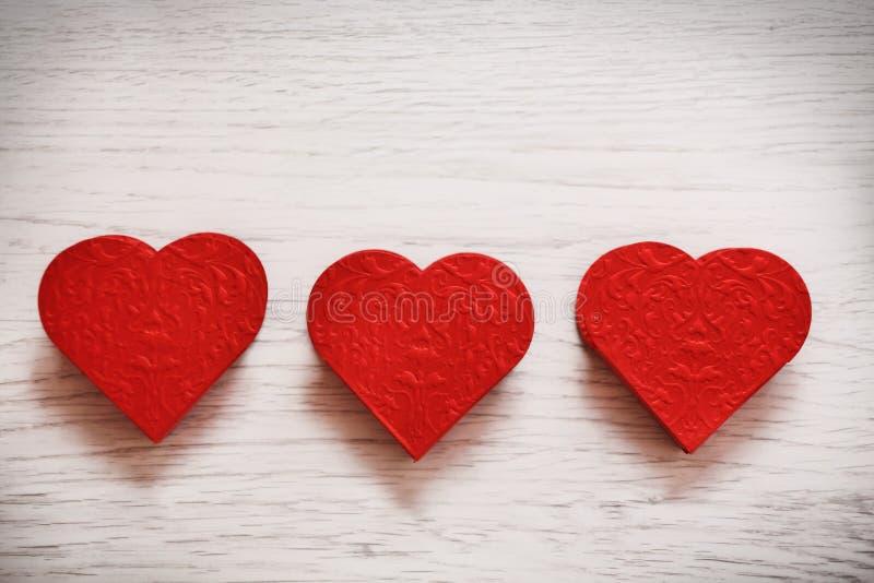 De achtergrond van de valentijnskaartendag met drie harten royalty-vrije stock afbeeldingen