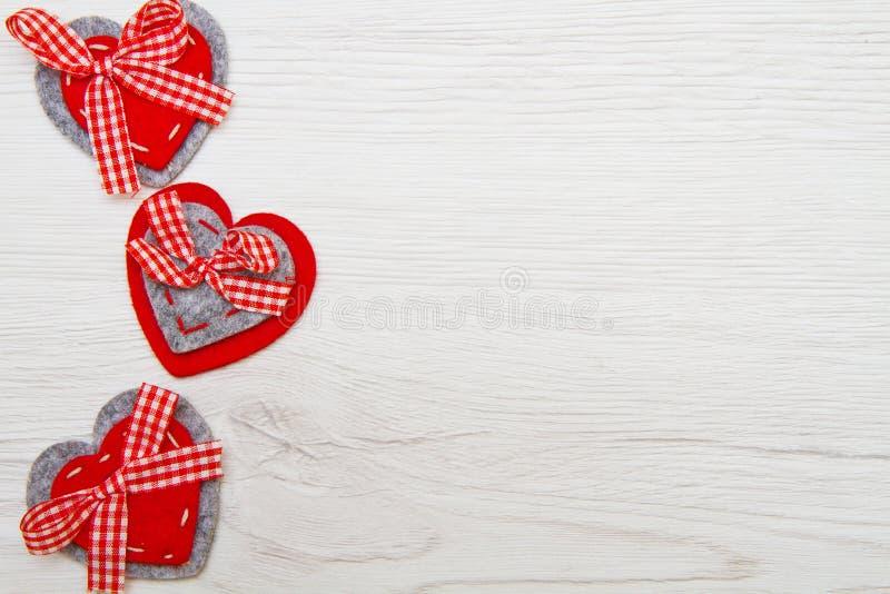 De achtergrond van de valentijnskaartendag met met de hand gemaakte stuk speelgoed harten over houten t royalty-vrije stock afbeeldingen